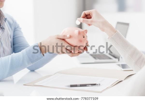 Финансовый консультант, в котором находится копилка, и клиент вставляет монету: депозит, сберегательный план и концепция пенсионного фонда