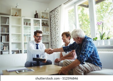 Financial advisor shaking hands with senior man in living room