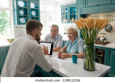 Financial advisor talks with elderly clients in their home. Cozy atmosphere and friendly attitude. Retirement planning concept.