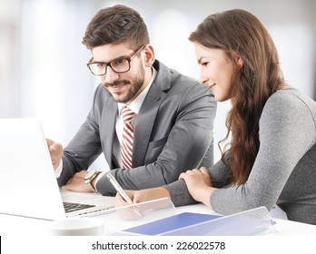 Financial advisors analyzing data on laptop while sitting at office.