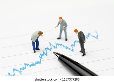 Financial analysis, investment consultant or advisor concept, miniature professional businessmen standing and looking, review on volatility blue stock market line graph data report with pen.