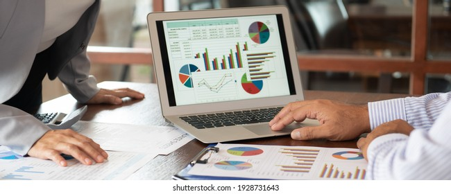 Financial analyst analysis business financial report on digital tablet during discussion at meeting of corporate showing the results of their successful teamwork.