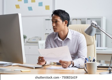 Financial analyst with document in his hands reading information on computer screen
