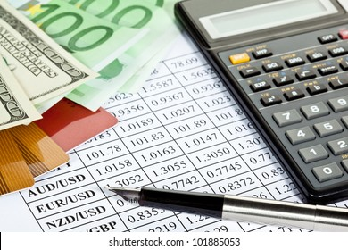 Financial analytics: money, plastic cards, calculator and a pen lying on a currency cross-rate table