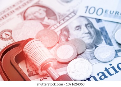 Financial austerity / budget control concept : Coins held by a c clamp on US dollar notes, depicts the economic policies a government implements to reduce budget deficits or control public sector debt