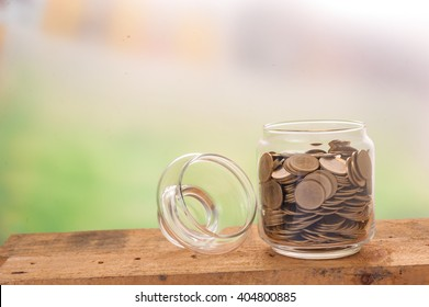 Financial background with money coins in clear bottle. World trade financing concept.