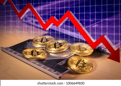 Financial bear market falling concept with Physical bitcoins over a laptop's CD drive and a red down arrow. Bitcoin and other cryptocurrencies ecnomic bubble or speculation concept