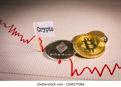 Financial bear market falling concept with physical bitcoin and ethereum over a red down chart and a flag with crypto word