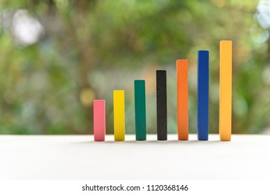 Financial business growth or sales performance increase concept : Increasing height, color wood bar graph on a table with green nature background, depicts an increase in product amount, extent, size