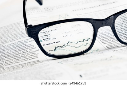 financial chart and graph currencies see through glasses lens on financial newspaper, business concept