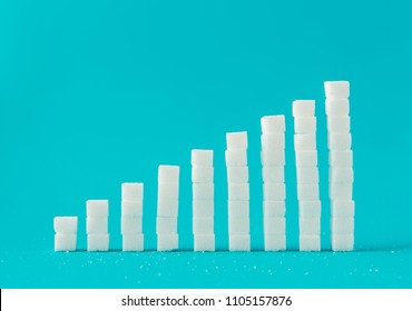 Financial chart made of sugar cubes with blue background. Sugar consumption growth rate world market concept.