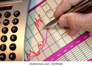 Financial chart, market's rising, calculator, pen, human hand.