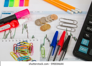 Financial chart on a white background with calculator, coins, pens, pencils, paper clips