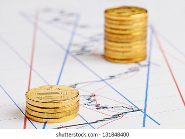 Financial  chart, rising stacks of golden coins. Selective focus