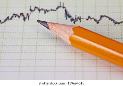 Financial chart of the stock market and pencil. Selective focus