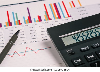 Financial charts and a calculator on the accountant's desk. Preparing a report, analyzing the company's income and expenses. Calculating profits, taxes, and paying employees salaries.