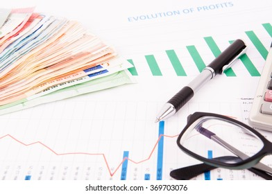 Financial charts with glasses, calculator, pen and euros