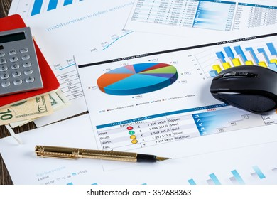 financial charts and graphs and a pen on the office table