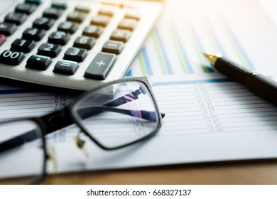 financial charts on the table with laptop, calculator, pen and glasses business concept.