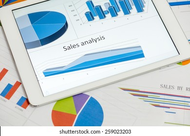 Financial charts on the table with tablet