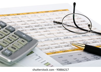 Financial charts with pen, calculator and glass.