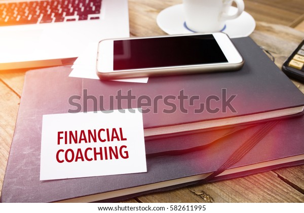 Financial Coaching on business card with text on office desktop with electronic devices, sun lit with lens flares.
