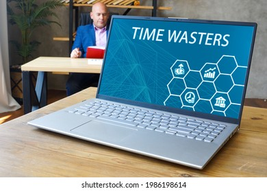 Financial concept about TIME WASTERS with inscription on the computer.