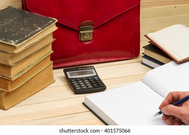 Financial concept. Businessman counting profit and losses, analyzing financial results. On a wooden table books, documents, calculator, red briefcase.