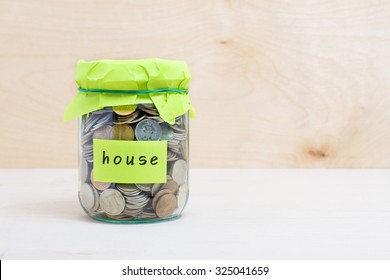 Financial concept. Coins in glass money jar with house label. Wooden background