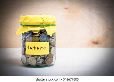 Financial concept. Coins in glass money jar with future label. Wooden background