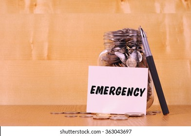 Financial concept. Coins in glass money jar with emergency label. Wooden background