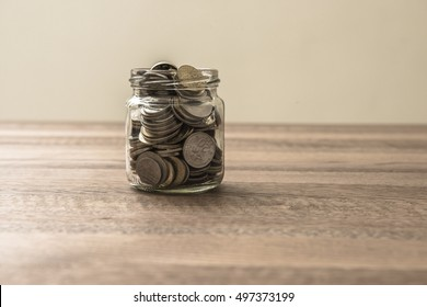 Financial concept. Coins in glass money jar on wooden background