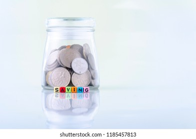 financial concept, colorful alphabet letter dice text on white reflection table, spelling SAVING over glass jar with coins