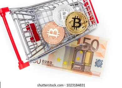 Financial concept with image of bitcoins in shopping cart on fifty euro banknote. Traditional money versus cryptocurrency concept.