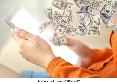 Financial concept. Make money on the Internet. Female hand holding PC tablet on home interior background