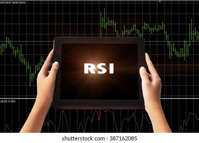 """Financial Concept. Relative Strength Index """" RSI"""" words in white color on tabled in hands and technical bar chart  background."""