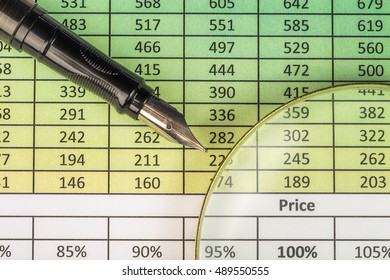 Financial concept. Report with digits, fountain pen and magnifying glass.