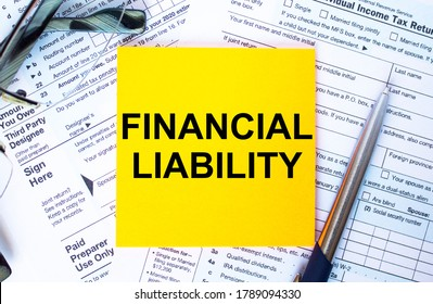 Financial concept. Text Financial Liability on note paper with the U.S IRS 1040 form,pen and glasses