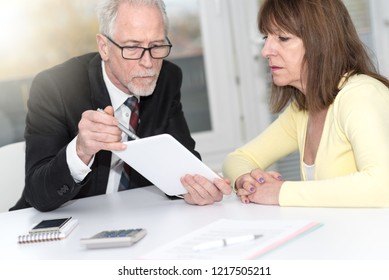 Financial consultant giving advices to female client, light effect