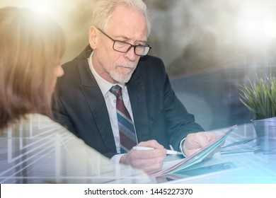 Financial consultant giving advices to female client, light effect; multiple exposure
