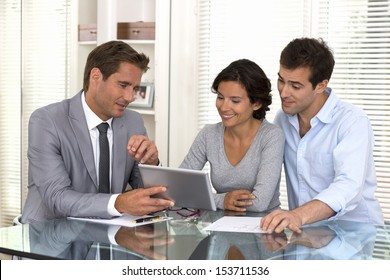 Financial consultant presenting a new project investment to a smiling young couple