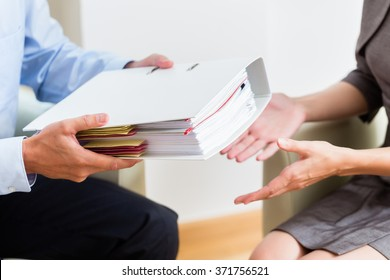 Financial consulting - customer handing over documents to consultant for further analysis