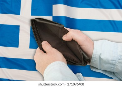 Financial Crisis in Greece - Man's Hand With Empty Wallet With Flag in Background