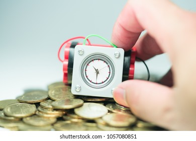Financial crisis into a business opportunity, Time and Risk management concepts. Small Clock bomb holding by man hand over pile of golden coins.