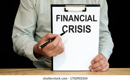 Financial crisis word written on a piece of paper. A man holds it and points to the word with a pen