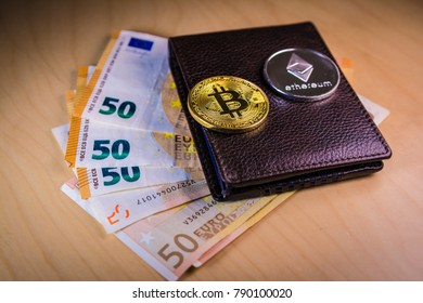 Financial cryptocoin concept with physical bitcoin and ethereum over a leather wallet with Euro bills.