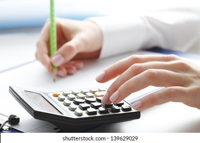 Financial data analyzing. Close-up photo of a businesswoman's hand writing and counting on calculator in office.  Selective focus