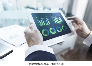 Financial data concept, close-up of modern businessman using tablet computer with charts on screen at office table