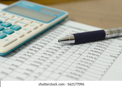 Financial data table and calculator on desk.