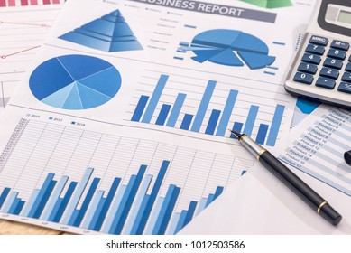Financial development - calculator and pen on chart and graph paper.